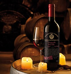 A bottle of Numerada 38 with a glass full of red wine and some candles, on top of a wine barrel