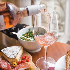 Pouring glass of rosé on a summer table of food