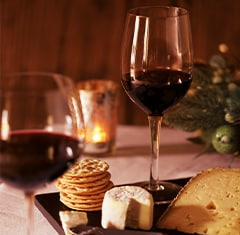 A cheese board and two glasses of red wine